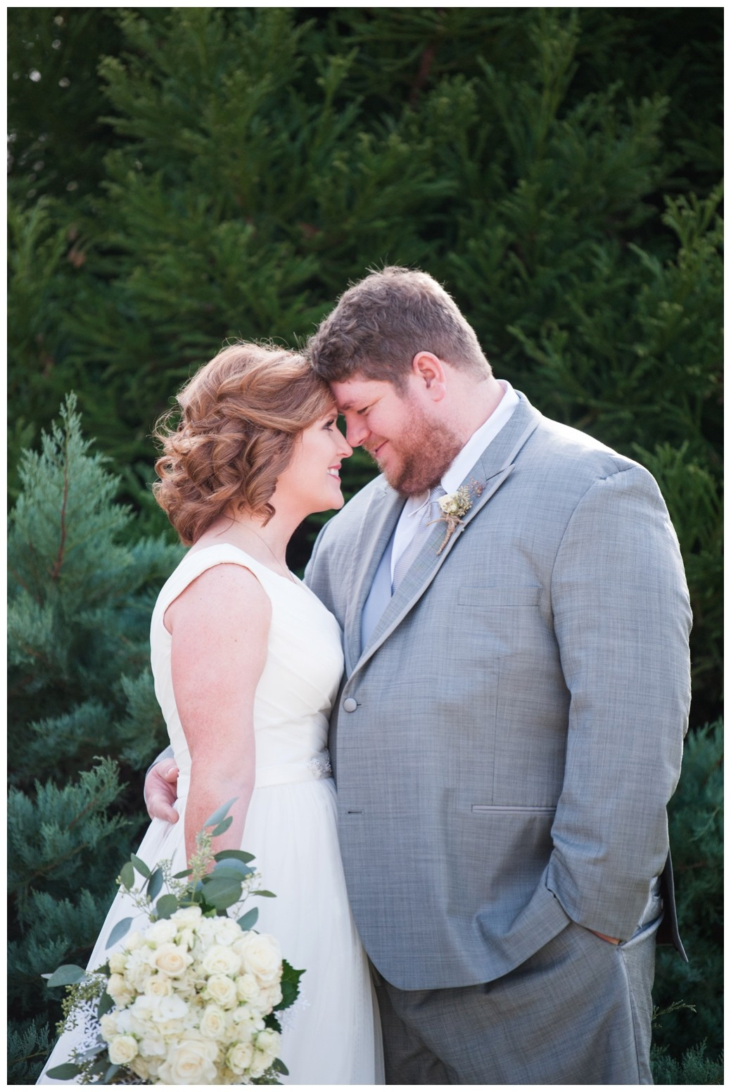 bride and groom smiling with foreheads together in front of greenery
