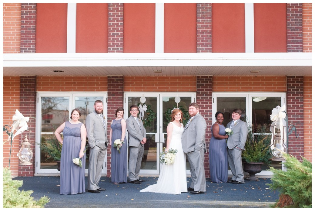 wedding party with blue grey dresses in front of church