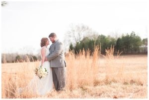 bride and groom in field standing in tall grass looking at one another