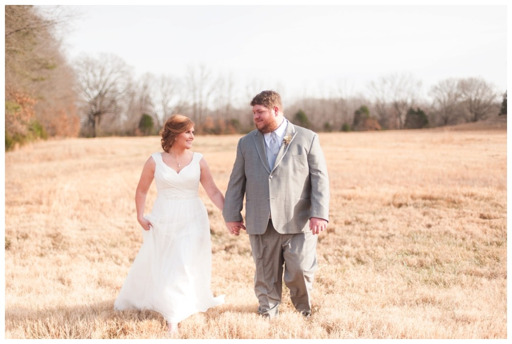 bride and groom walking through field looking at one another