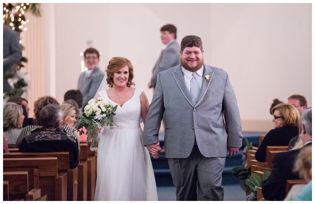 bride and groom coming down the aisle after wedding