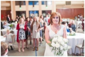 bride getting ready to throw bouquet to single girls standing behind her