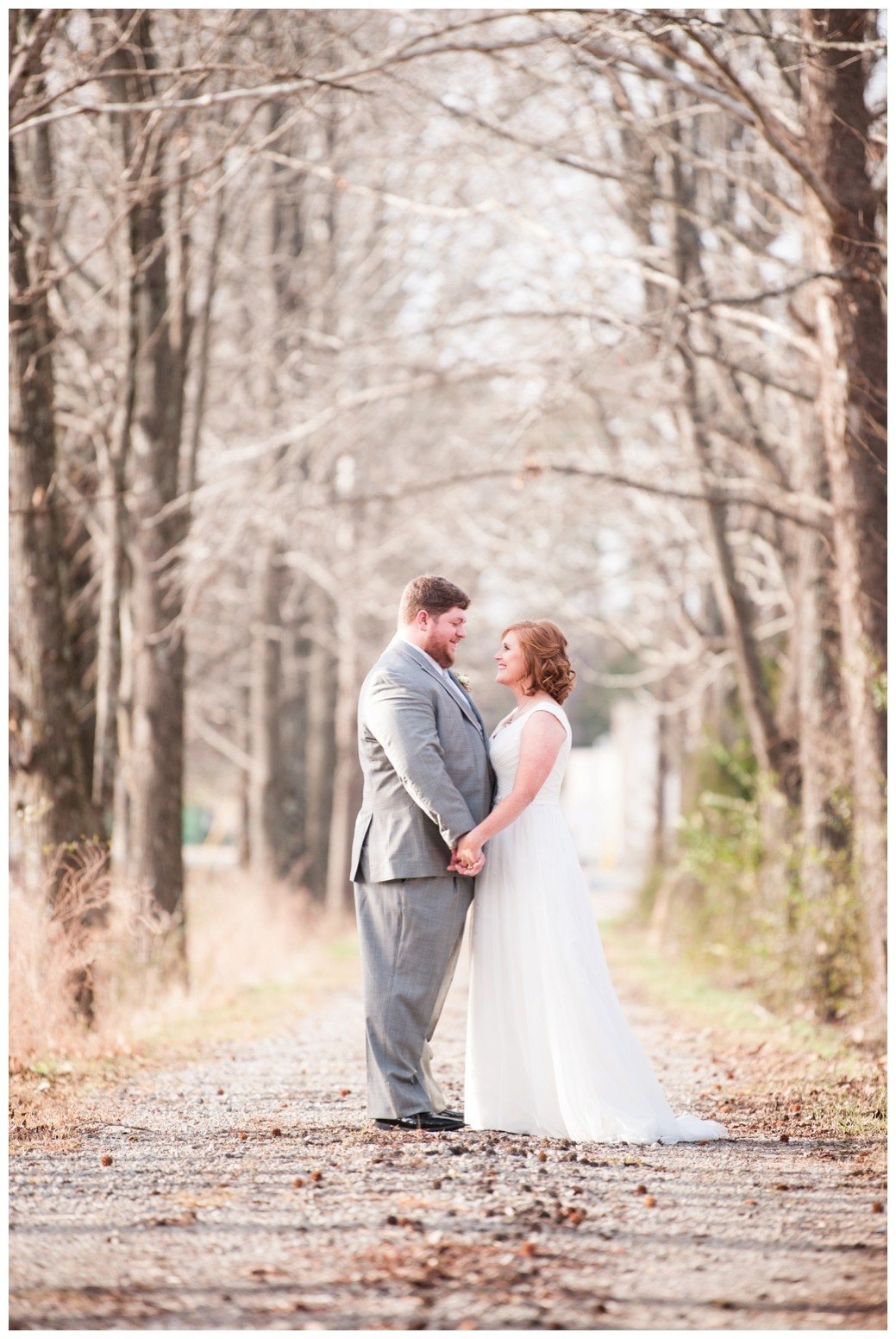 bride and groom on path looking at one another in winter
